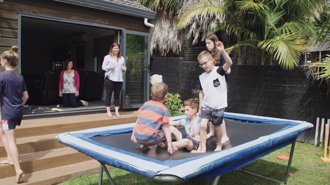 Four children play on a trampoline supervised by parents at a house.