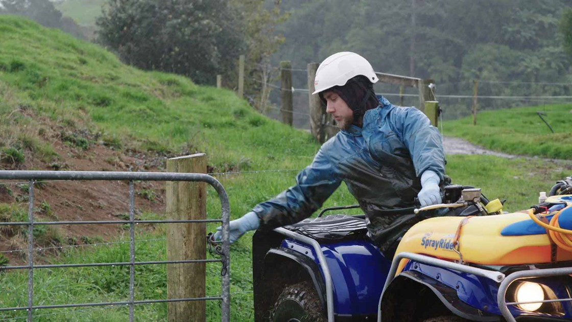 Jack on a quadbike closing a paddock gate dressed in wet-weather gear.
