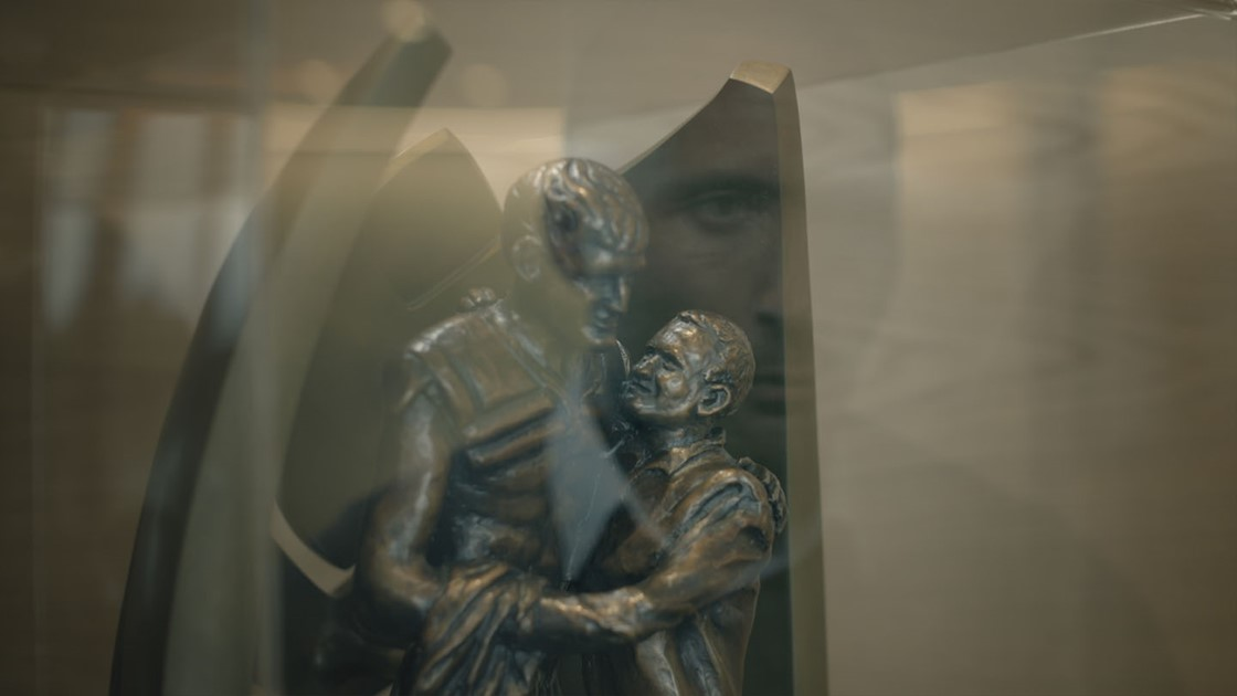 Paul's reflection overlaying a metal statue of a man and a boy hugging.