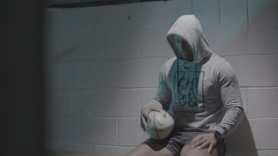 Paul hiding his face in a hoodie holding a rugby ball.